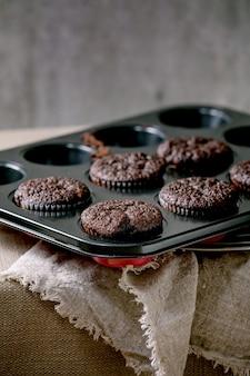 Queques de bolinhos de chocolate caseiros assados frescos em forma de cozinhar em pé na mesa da cozinha com toalha de mesa. padaria caseira