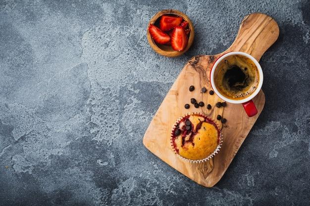Queques de cupcakes de morango e chocolate em um antigo suporte de madeira na superfície cinza de concreto