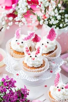 Queques do coelho no carrinho do bolo branco. sobremesa de páscoa
