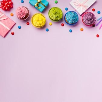 Queques e gemas coloridos com caixas de presente embrulhado em pano de fundo rosa