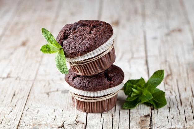 Queques escuros do chocolate com folhas de hortelã.