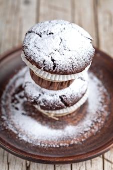 Queques escuros do chocolate com pó do açúcar na placa marrom na tabela de madeira rústica.