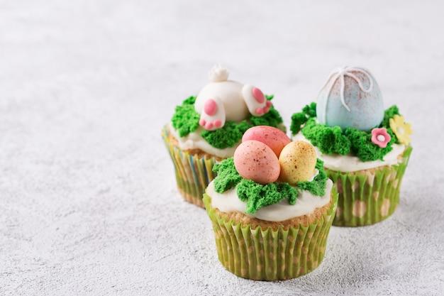 Queques festivos com ovos e grama de mástique no fundo brilhante. conceito de feriado de páscoa. espaço da cópia