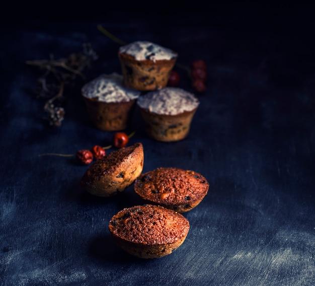 Queques redondos cozidos com uma mesa de madeira preta raisin, close-up