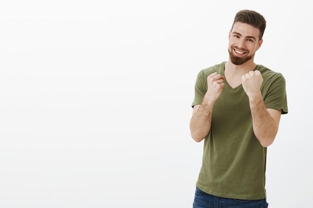 Quer lutar, venha e pegue. retrato de um homem barbudo bonito feliz, animado e brincalhão, com olhos azuis segurando os punhos como um boxeador pronto para socar, sorrindo sobre a parede branca