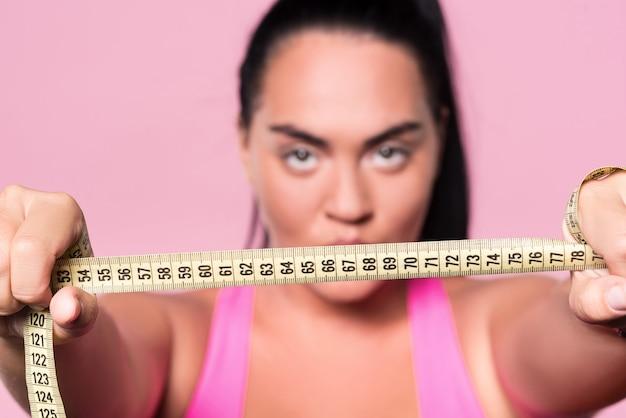 Querendo ser magro. close up de uma fita métrica de corpo segura por uma mulata gordinha