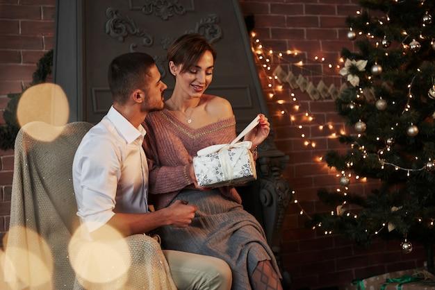 Queria ver o que havia dentro. lindo casal jovem na cadeira abraçando na sala de luxo que está decorada guirlandas e árvore de férias