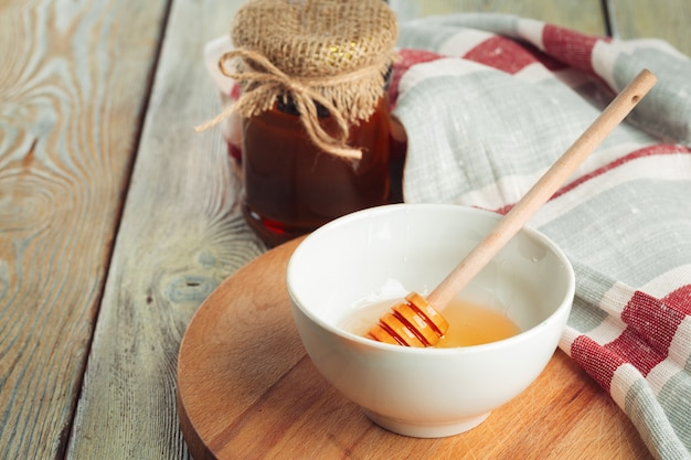 Querida. doce mel em frasco de vidro na madeira.