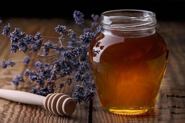 Querida em uma jarra de vidro, uma colher de mel, flores de lavanda em uma velha mesa de madeira.
