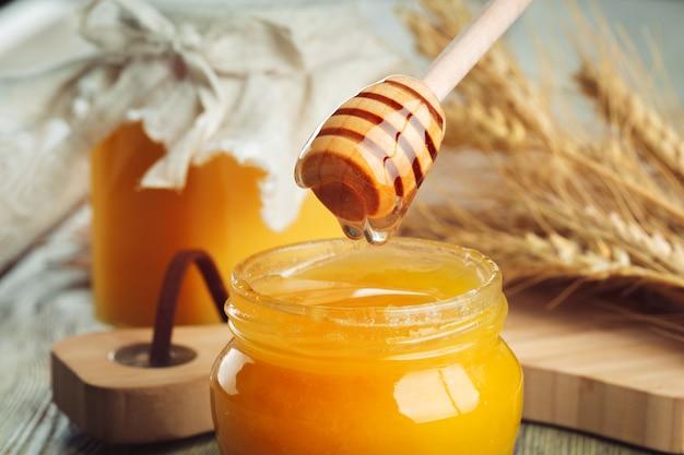 Querida . mel doce em frasco de vidro em madeira.