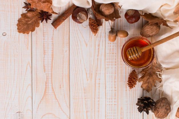 Querida, pau, pote, cachecol, folhas secas. foto doce rústica do outono, fundo de madeira branco, copyspace.