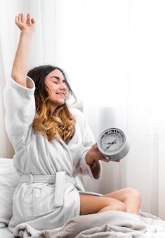Querida satisfez a menina manhã na cama com relógio, conceito de tempo e uma boa noite de sono