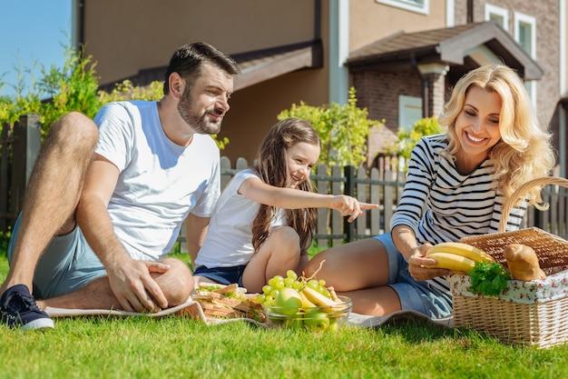 Quero isso. linda garotinha sentada entre os pais no piquenique e apontando bananas, pedindo à mãe que as desse a ela