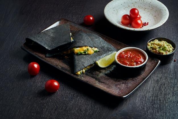 Quesadilla assado apetitoso com 4 tipos de queijo em tortilha preta em um prato de cerâmica em uma mesa preta ... cozinha mexicana moderna.