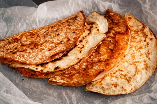 Quesadilla mexicana caseira é empilhada em um pergaminho.