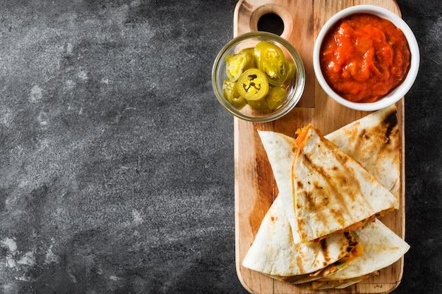 Quesadilla mexicana com frango, queijo e pimentos em fundo preto