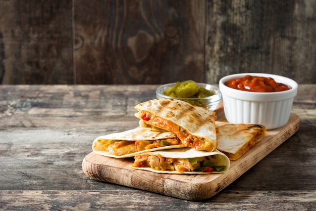 Quesadilla mexicana com frango, queijo e pimentos na mesa de madeira