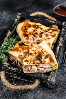 Quesadilla mexicana com frango, tomate, milho e queijo na mesa preta. vista do topo.