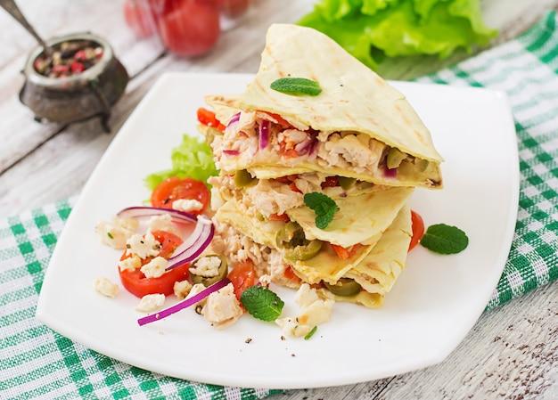 Quesadilla mexicano enrole com frango, azeitonas, pimentão e salada.