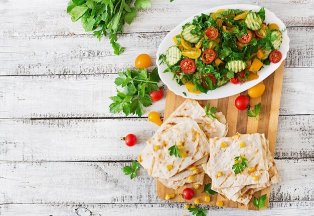 Quesadilla mexicano enrole com frango, milho e pimentão e salada fresca.