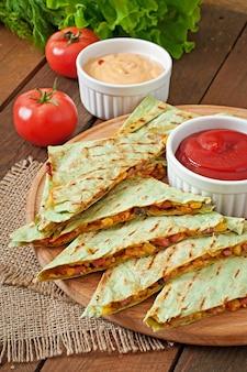 Quesadilla mexicano fatiado com legumes e molhos em cima da mesa
