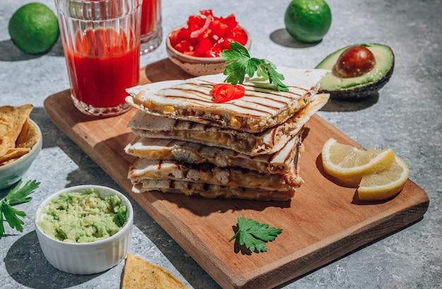 Quesadillas grelhadas na placa de madeira e com molho e guacamole no fundo de pedra. conceito de cozinha mexicana quesadilla wrap com frango e milho. foco seletivo. longas sombras
