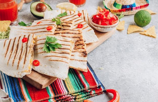 Quesadillas grelhadas na placa de madeira e com molho e guacamole no fundo de pedra. conceito de cozinha mexicana quesadilla wrap com frango e milho. foco seletivo