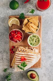 Quesadillas grelhadas na placa de madeira e com molho e guacamole no fundo de pedra. conceito de cozinha mexicana quesadilla wrap com frango e milho. vista do topo