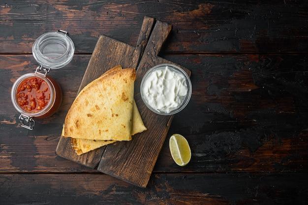 Quesadillas grelhadas ou tortilhas com mistura de queijo, em fundo de mesa de madeira escura, vista de cima plana com espaço de cópia para o texto