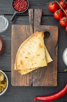 Quesadillas ou tortilhas grelhadas com mistura de queijo, em fundo preto de mesa de madeira, vista de cima plana lay