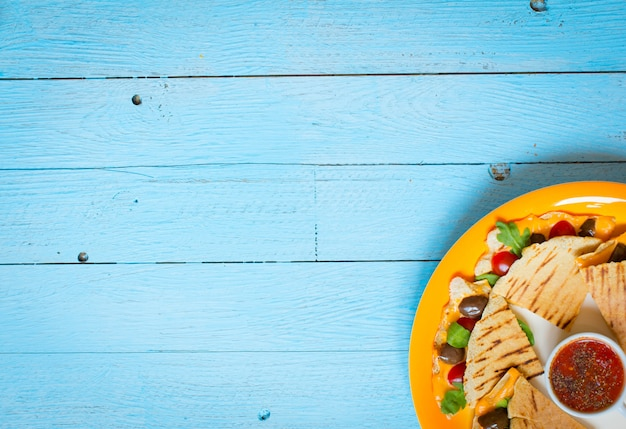 Quesadillas vegetarianos deliciosos no fundo de madeira azul