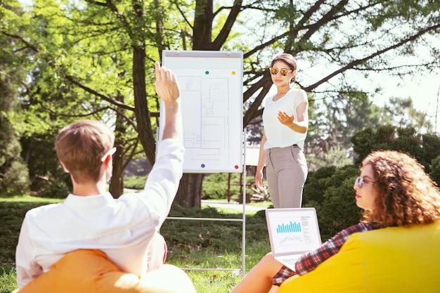 Questão importante. garota séria e magra em pé no quadro e discutindo seu projeto com os colegas de grupo