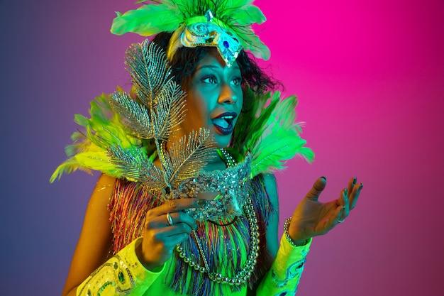 Questionado. mulher jovem e bonita no carnaval, elegante traje de máscaras com penas dançando na parede gradiente em neon. conceito de celebração de feriados, tempo festivo, dança, festa, diversão.