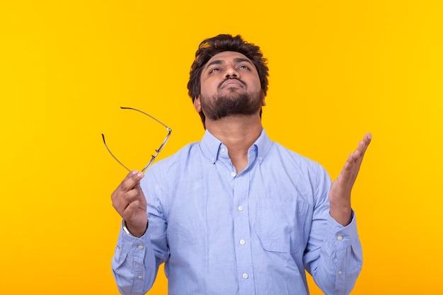 Questionador frustrado do jovem empresário levantou a cabeça e as mãos até o topo, posando em uma parede amarela. conceito de fracasso. copyspace