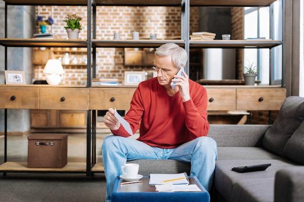 Questões de negócios. homem sênior sério e simpático sentado à mesa de centro fazendo uma ligação enquanto trabalhava em casa
