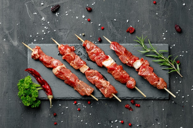 Quibe de carne crua com ervas em uma placa escura, close-up