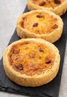 Quiche caseira lorraine sobre a tábua de pedra. torta tradicional de bacon e queijo.