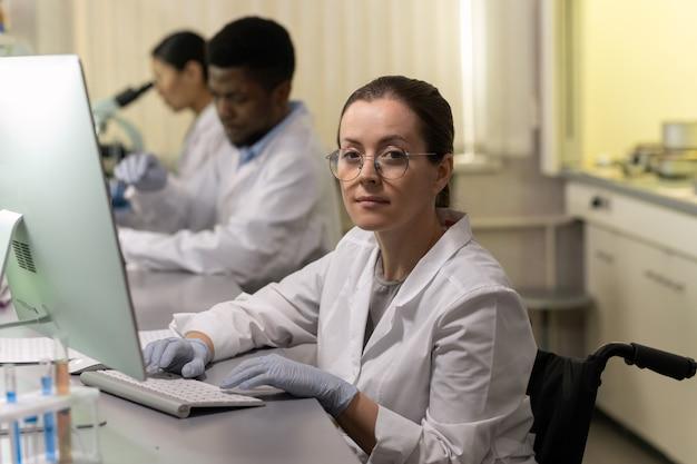 Química confiante usando computador por local de trabalho contra dois colegas