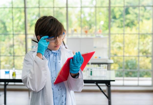 Química do studing do menino na sala do laboratório na escola conceito da ciência e da educação.