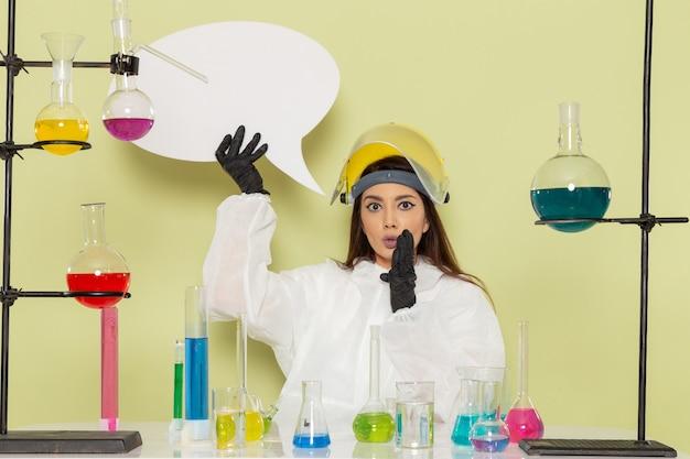 Química feminina com roupa de proteção especial, vista frontal, segurando uma grande placa branca na superfície verde-clara