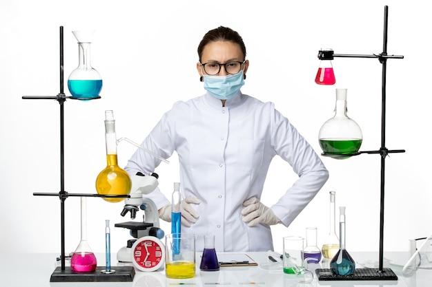 Química feminina de frente para o terno médico com máscara posando no fundo branco do laboratório de química do vírus - respingo