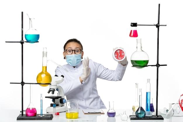 Química feminina de frente para o terno médico com máscara segurando relógios no fundo branco vírus laboratório química respingo secreto