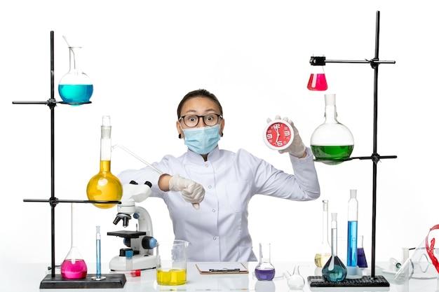 Química feminina de frente para o terno médico com máscara segurando relógios olhando para o pulso dela no fundo branco vírus laboratório química covid- splash
