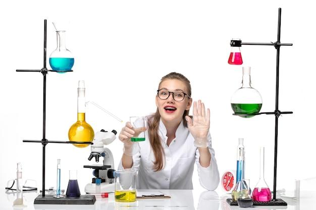 Química feminina de frente para o terno médico segurando o frasco com a solução na luz de fundo branco. química pandêmica saúde covid