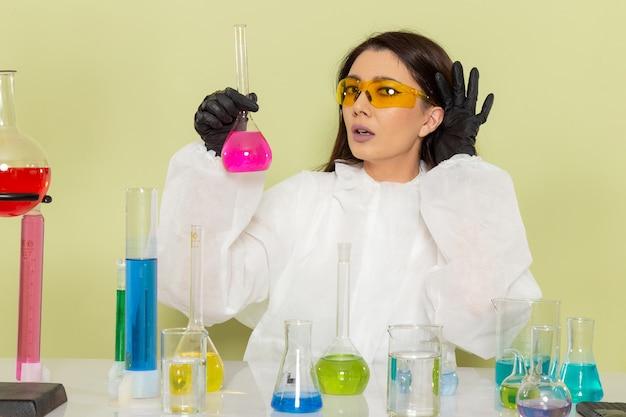 Química feminina de vista frontal em traje de proteção especial trabalhando com soluções na superfície verde claro