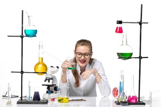 Química feminina em terno médico, vista frontal, verificando o cheiro da solução e rindo sobre fundo branco.