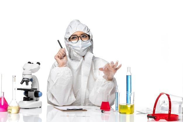 Química feminina em traje de proteção especial escrevendo notas sobre um fundo branco química de vírus covid pandemia de vista frontal