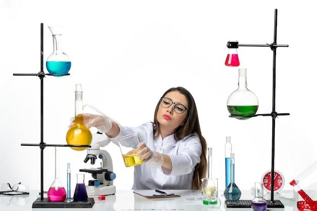 Química feminina em traje médico de frente, trabalhando com soluções em ciência de vírus de laboratório covidêmico de fundo branco