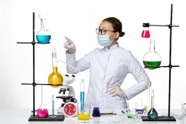 Química feminina em traje médico de frente, usando máscara e apontando no fundo branco, laboratório de química de vírus covid- respingo