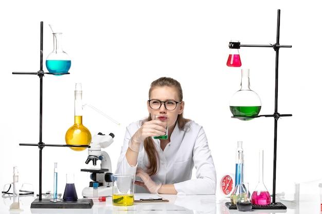 Química feminina em traje médico de frente, verificando o cheiro da solução no fundo branco. química, pandemia, saúde, covid